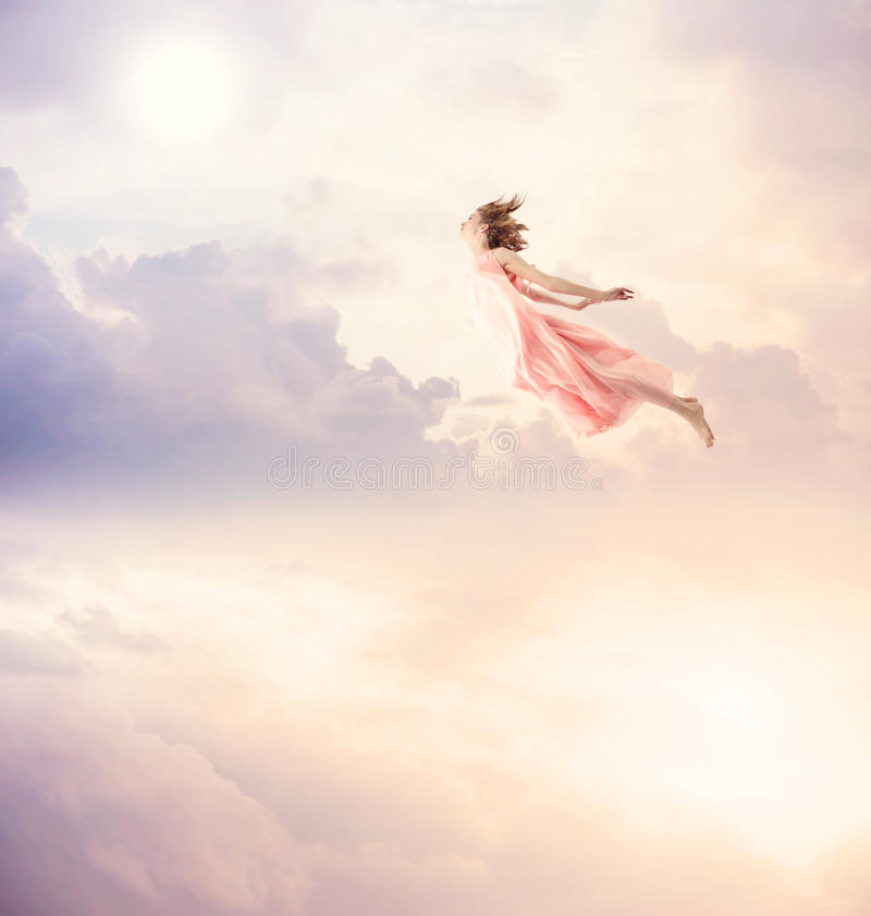 Girl in a pink dress flying in the sky. Serenity royalty free stock photography