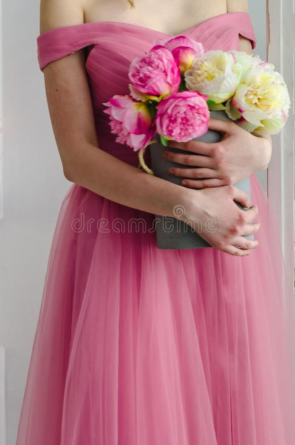 Girl in pink dress holding a basket of flowers royalty free stock photography