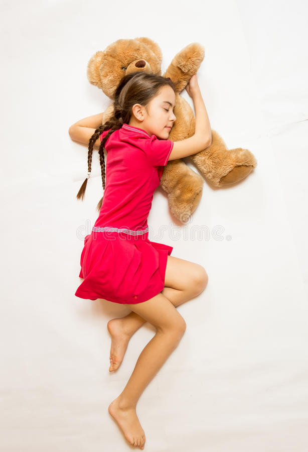 Girl in pink dress sleeping on big teddy bear on floor. Cute girl in pink dress sleeping on big teddy bear on floor stock photo