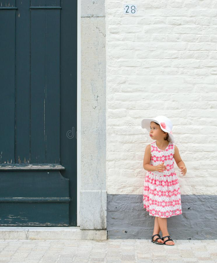 Girl in pink dress and white summer hat outdoor stock image