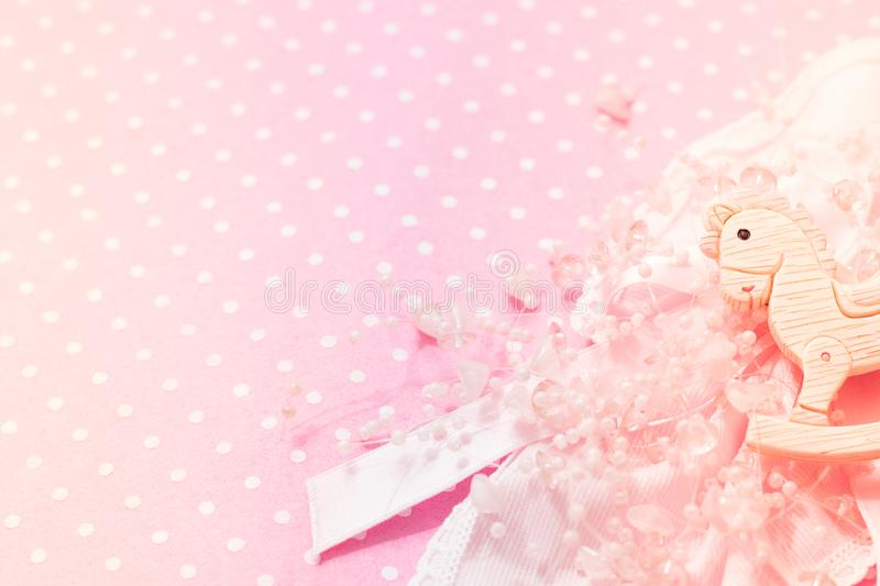 Girl pink felt background Baby Shower party with little rocking pony toy, lace and beads decor. Copy space. Top view. stock photography