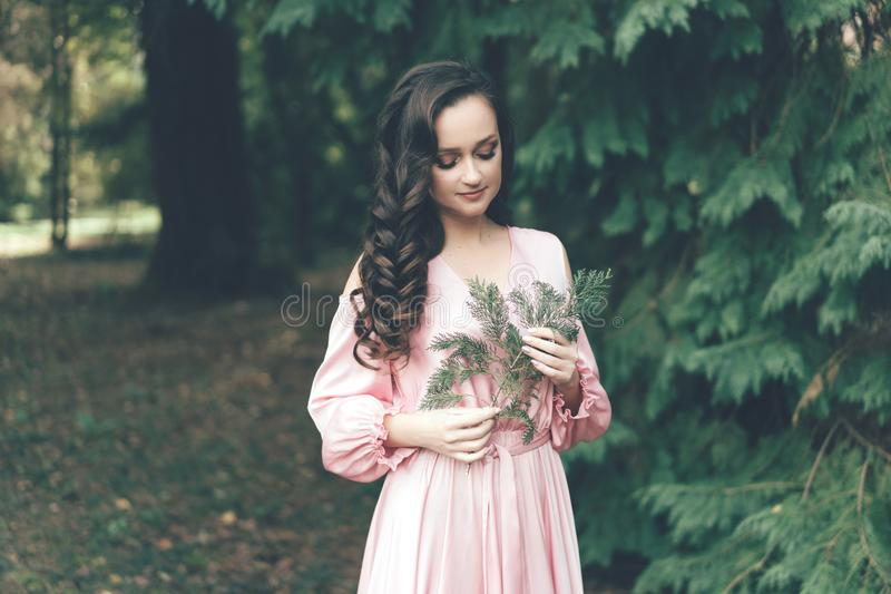 Girl in a pink gentle dress in the park stock photos