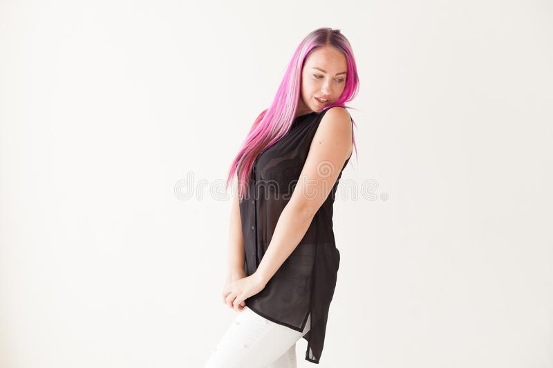 Girl with pink hair sits in a Chair in a white room stock photography