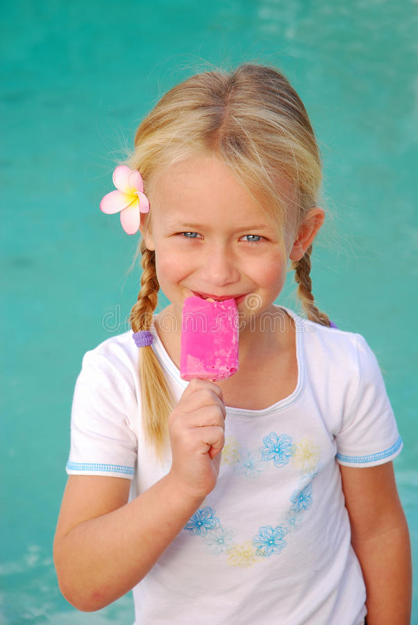Girl with pink ice-cream. A cute little Caucasian girl child with happy smiling facial expression eating a pink sorbet ice-cream royalty free stock photos