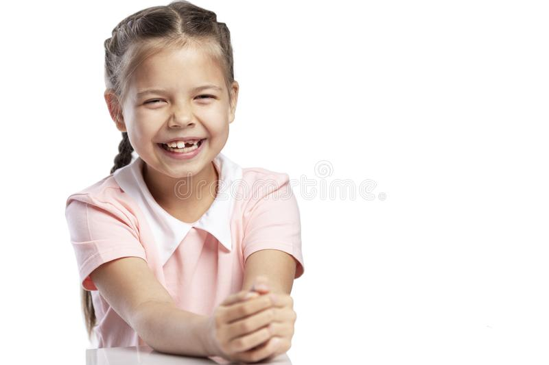 A girl in a pink jacket of a school age without a front tooth laughs. Close-up. Change of teeth. Isolated over white background. Horizontal stock photos
