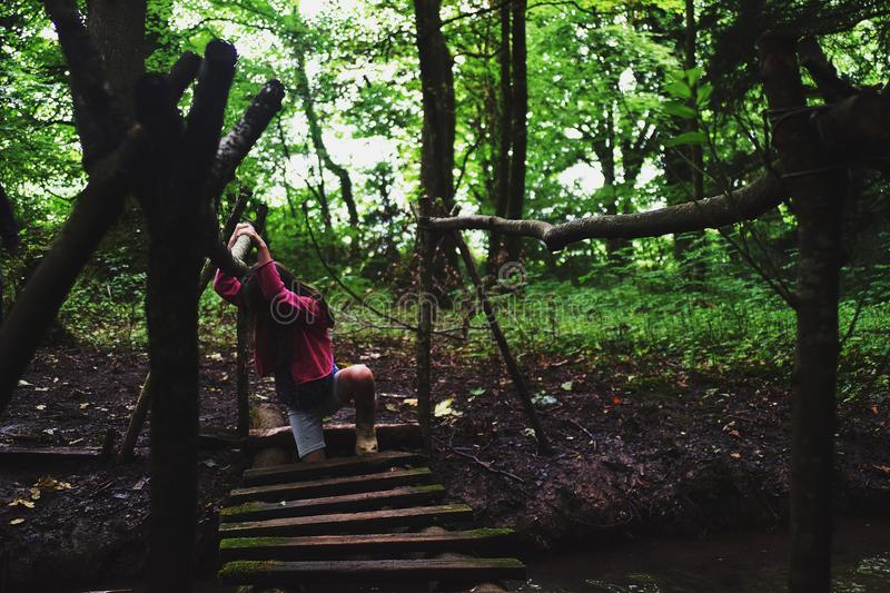 Girl in Pink Jacket on Wooden Bridge in the Forest royalty free stock photography
