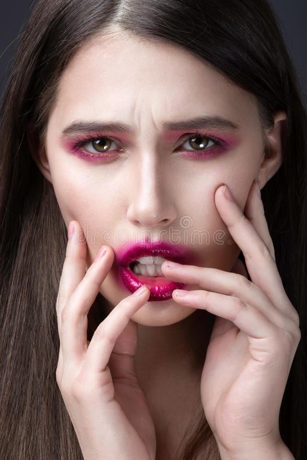 Girl with pink lipstick smeared across his face. Creative makeup. stock photos