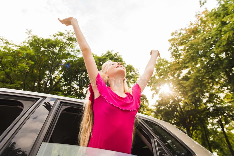 Girl in pink put hands up from automobile royalty free stock image