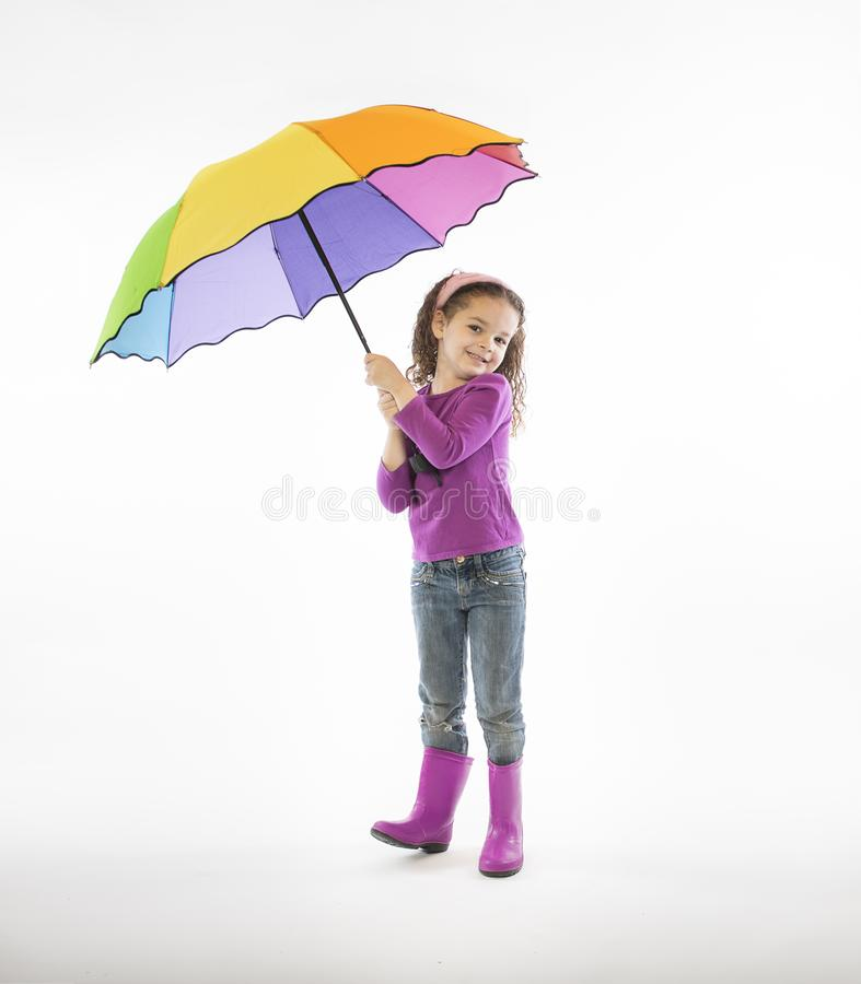 Girl in pink rain boots with rainbow umbrella royalty free stock photography