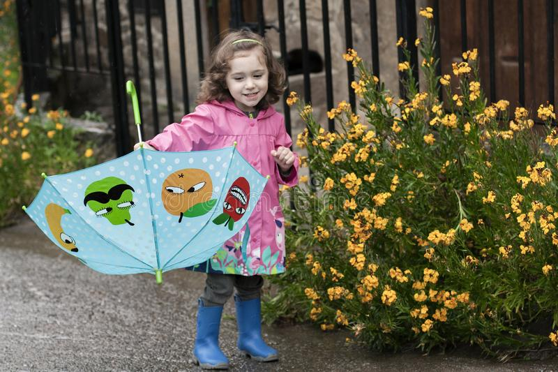 A little girl playing with a colorful umbrella. A girl in pink raincoat plays with her umbrella next to some yellow flowers, on a rainy day stock images