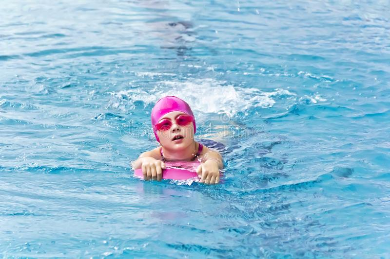 Girl in pink rubber hat. Cute girl with pink rubber hat are swimming in pool stock photo