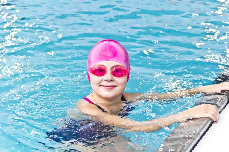 Girl in pink rubber hat. Photo of cute girl in swimming pool royalty free stock images
