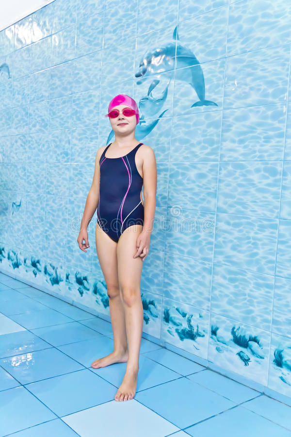 Girl in pink rubber hat. Photo of cute girl in swimming pool stock image