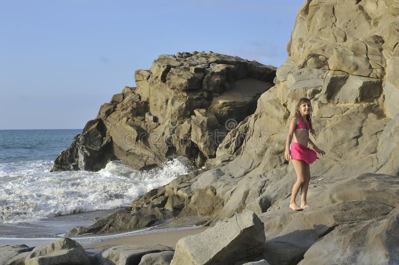 A girl in pink swimming costume on the rocky beach. stock photography