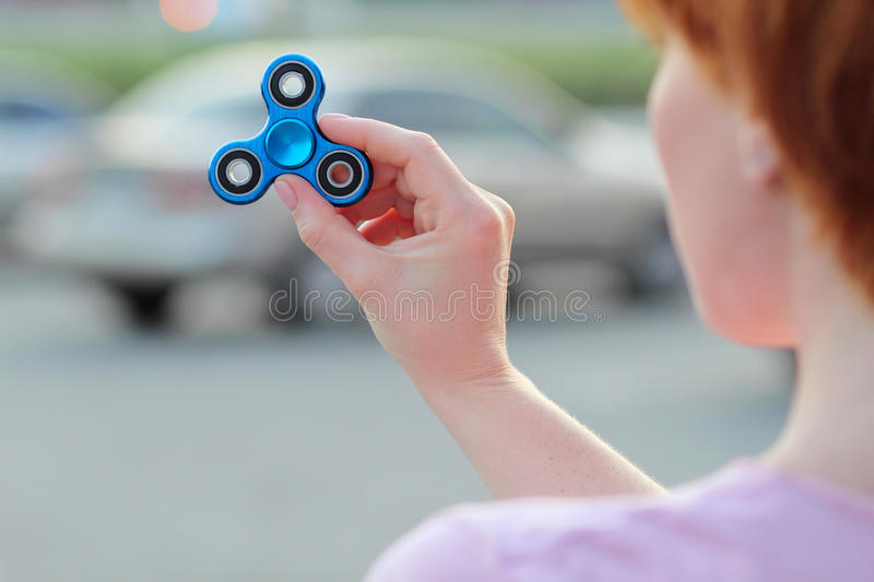 Girl in pink t-shirt is playing blue metal spinner in hands on the street, woman playing with a popular fidget spinner toy, anxiet stock image