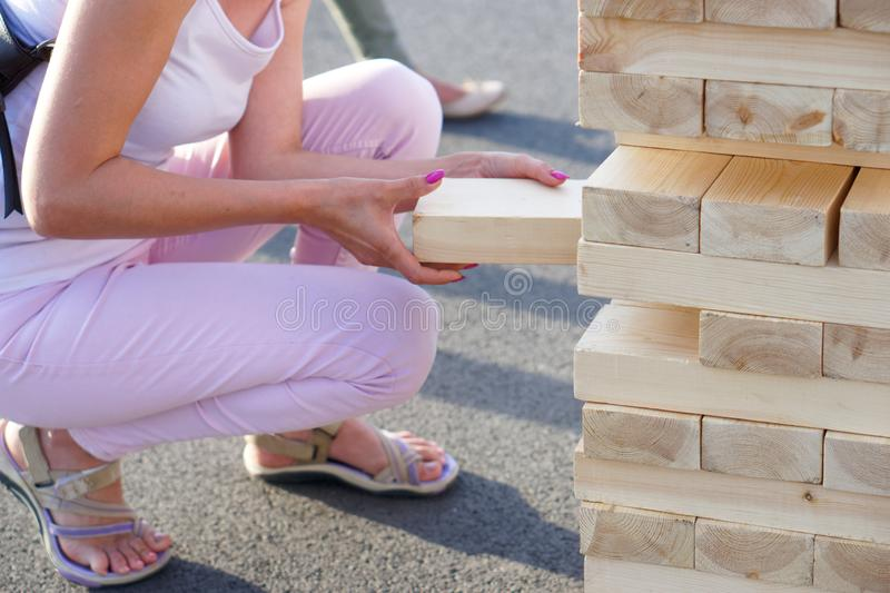 A girl in pink takes out one bar from the tower while playing a giant jenga. Outside royalty free stock photos
