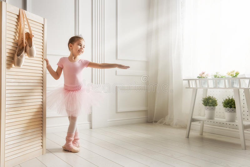 Girl in a pink tutu. Cute little girl dreams of becoming a ballerina. Child girl in a pink tutu dancing in a room. Baby girl is studying ballet stock images