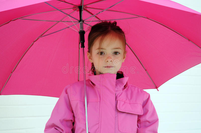 Girl with pink umbrella. Little girl dressed in pink, her favorite color. She holds in her hand an umbrella in the same color stock images