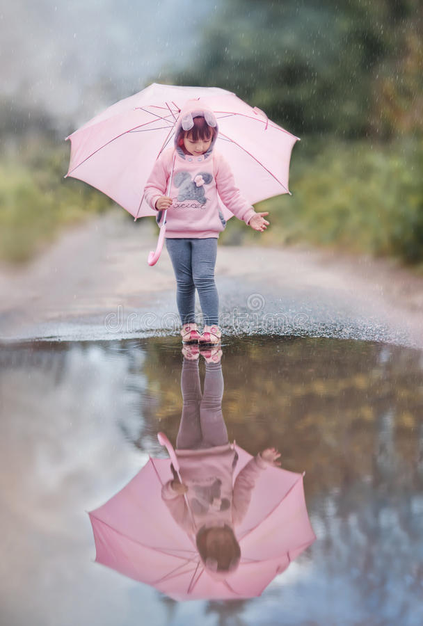 Girl with pink umbrella. Near puddle on rainy day stock image