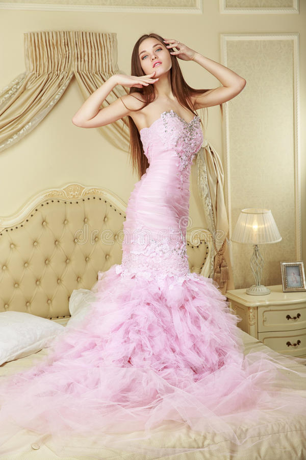Girl in pink wedding dress staying on the bed stock photography