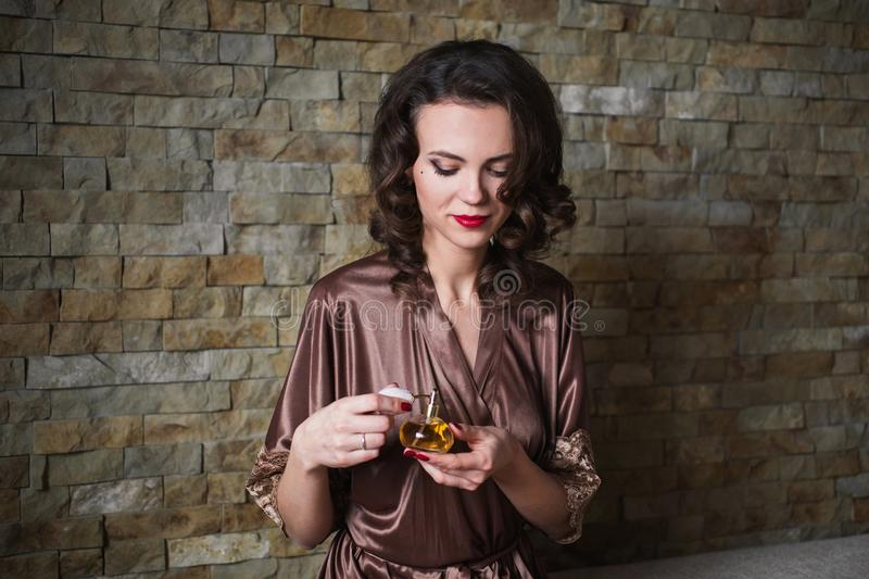 Girl PinUp with brunette hair and retro make-up with red lips in a bathrobe on a dark background. stock photos