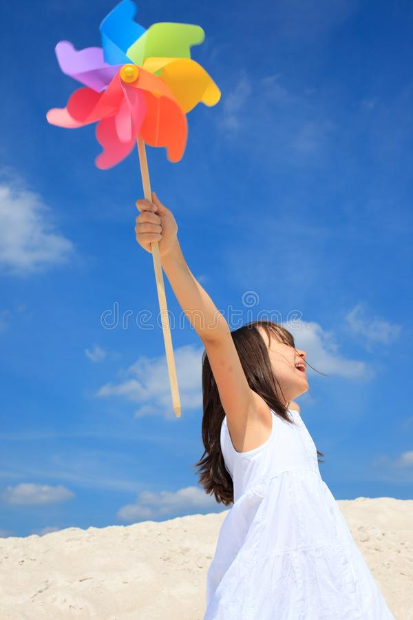 Girl with pinwheel on beach royalty free stock photography