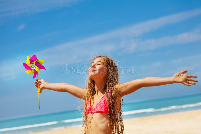 Girl with pinwheel on the beach happy and relaxed stock photography