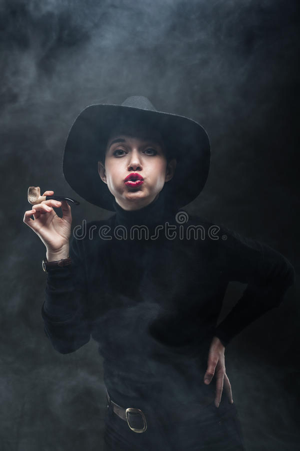 Girl with a pipe. Girl in black holding a pipe and blowing the smoke towards camera royalty free stock photography