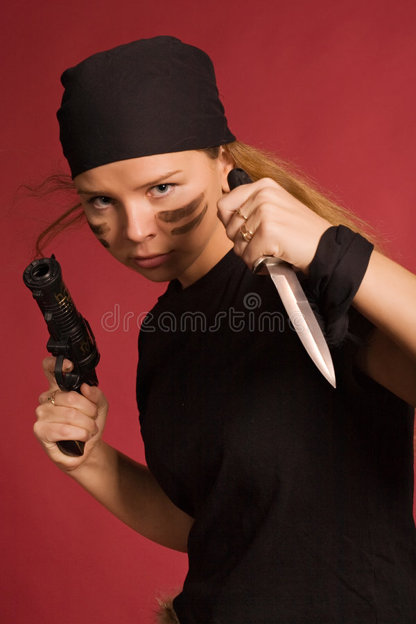 Girl in pirate costume. Beautiful girl in pirate costume with knife and pistol royalty free stock photo