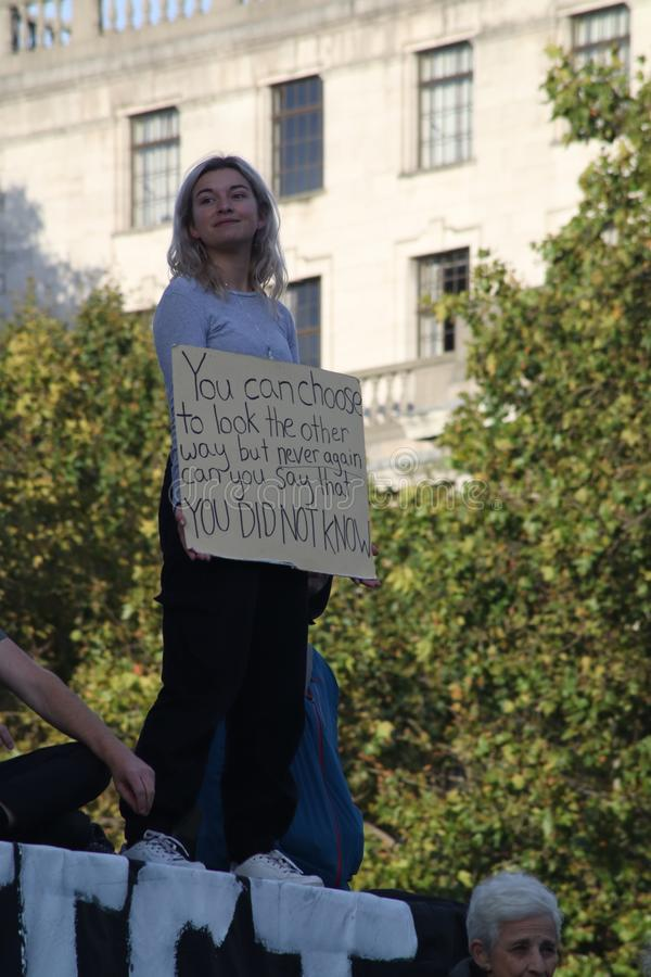 Girl With Placard On Nelson`s Column at Extinction Rebellion Protest. royalty free stock images