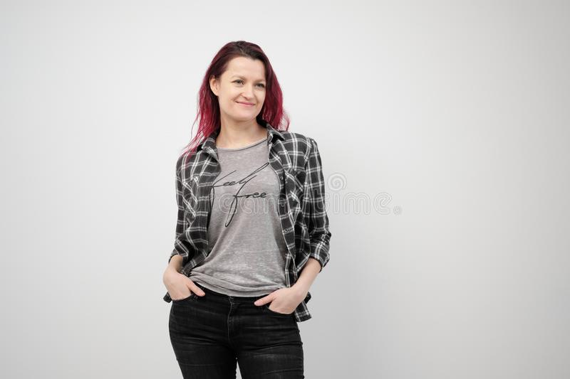The girl in a plaid gray shirt on a white background with dyed red hair. royalty free stock images