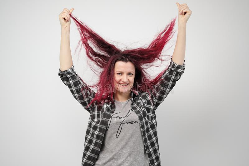 The girl in a plaid gray shirt on a white background with dyed red hair. royalty free stock image