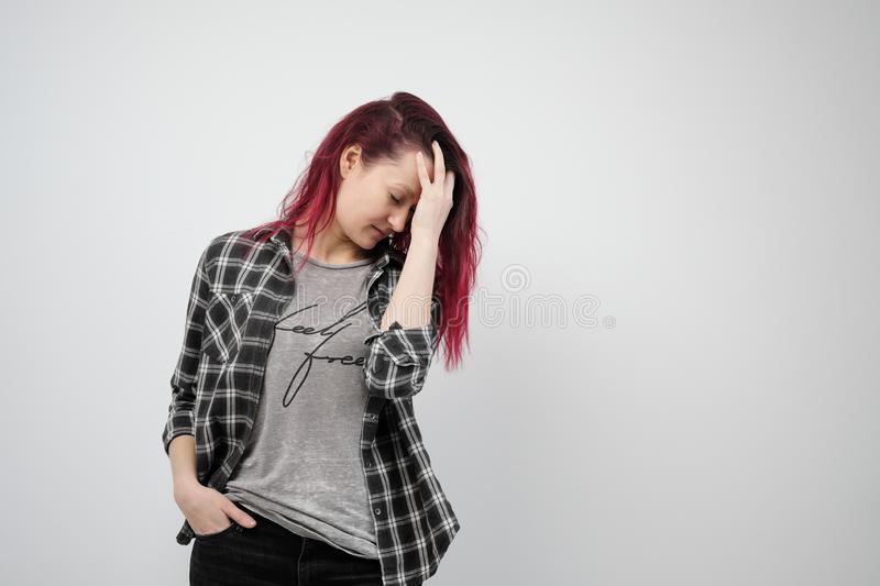 The girl in a plaid gray shirt on a white background with dyed red hair. stock images
