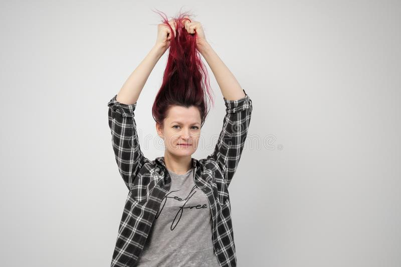 The girl in a plaid gray shirt on a white background with dyed red hair. stock image