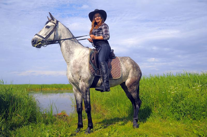 Girl in plaid shirt and cowboy hat riding a horse stock image