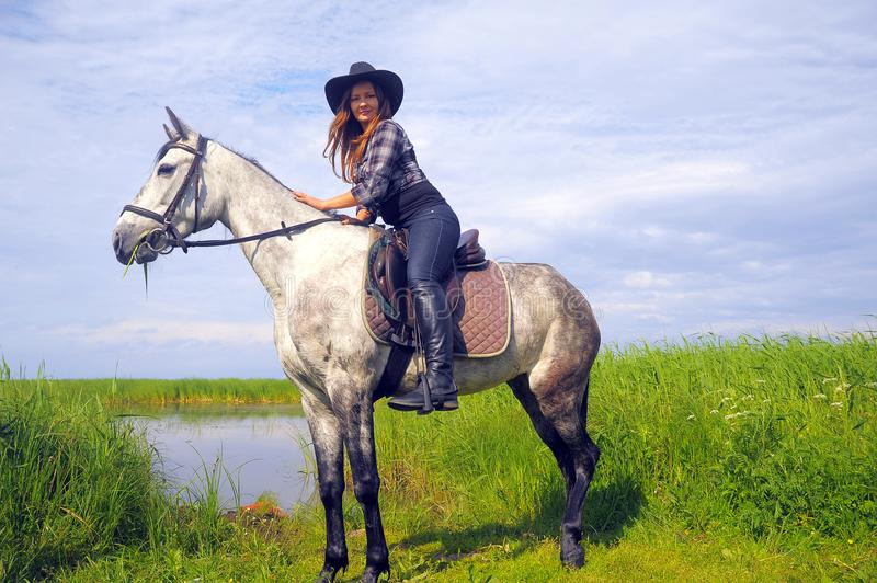Girl in plaid shirt and cowboy hat riding a horse stock photo