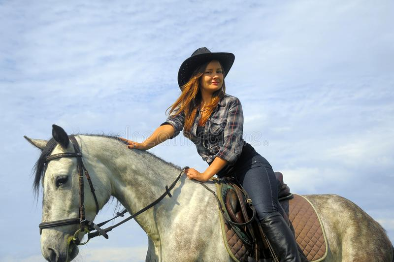 Girl in plaid shirt and cowboy hat riding a horse royalty free stock photography