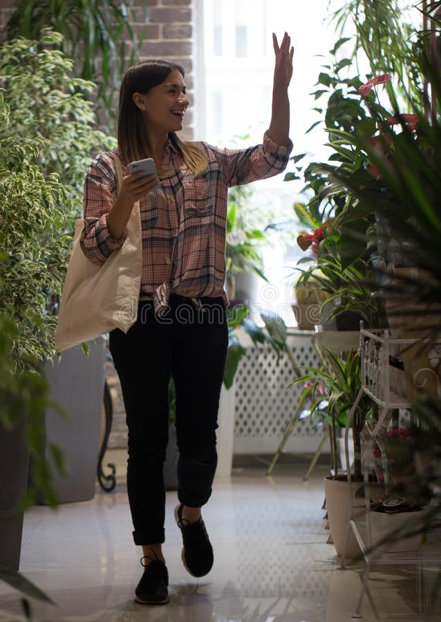 Girl in a plaid shirt with eco bag comes into the store and greets the sellers. A girl in a plaid shirt with eco bag comes into the store and greets the sellers stock photography