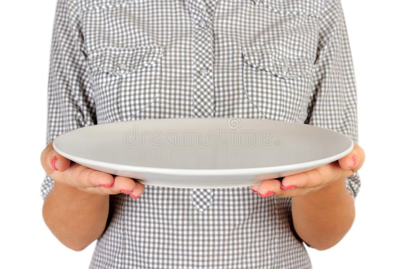 Girl in the plaid shirt is holding an empty round matte plate in front of her. woman hand hold empty dish for you desing. perspect royalty free stock images