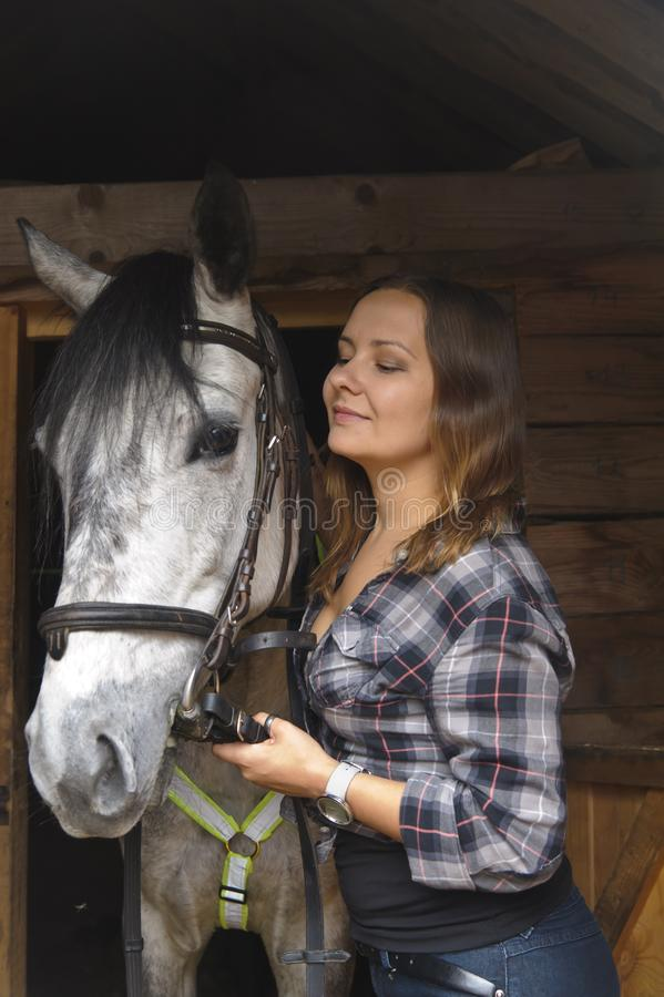 Girl in plaid shirt with a horse stock images