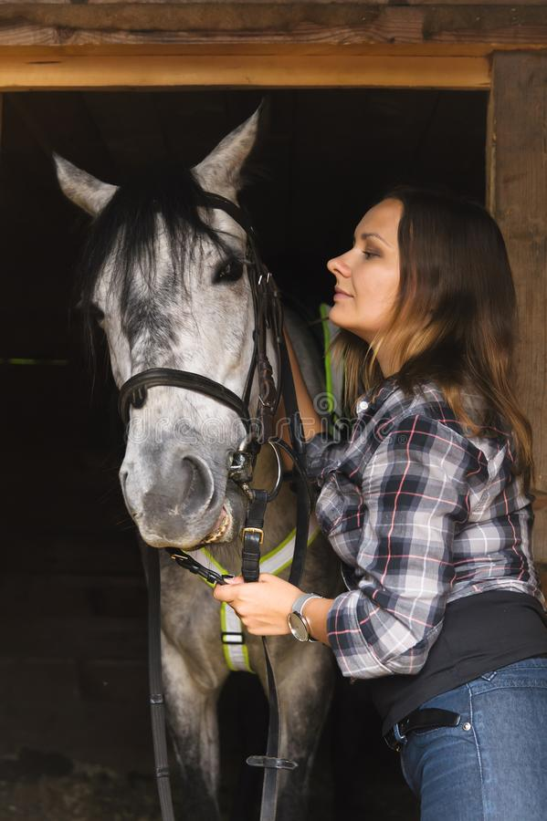 Girl in plaid shirt with a horse stock image