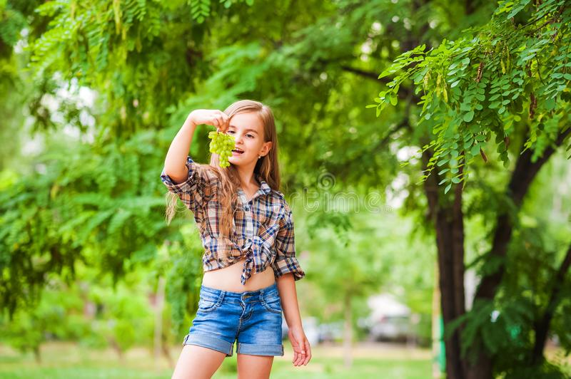 Girl in a plaid shirt and jeans holding a bunch of green grapes close-up. Concept of harvesting a plantation of grapes and a girl. Copy space stock photography
