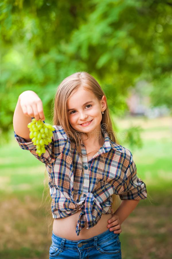 Girl in a plaid shirt and jeans holding a bunch of green grapes close-up. Concept of harvesting a plantation of grapes and a girl. Copy space royalty free stock photography