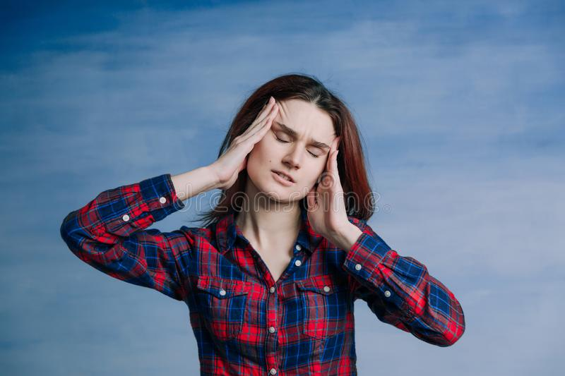 A girl in a plaid shirt twisted her face in pain and raises her hands to her face. On blue background royalty free stock photo