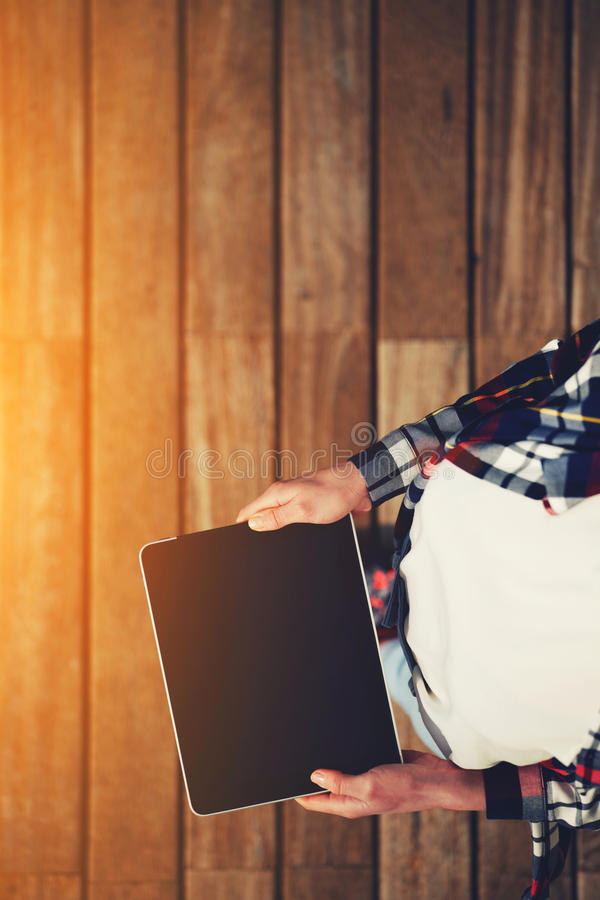 Girl in plaid shirt and white T-shirt holding digital tablet royalty free stock photo