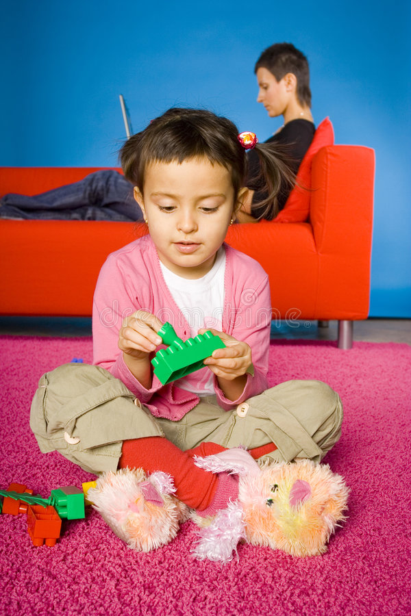 Girl is plaing with toy blocks (mother behind her). Girl sitting on the carpet and playing blocks and her busy (with laptop) mother on the sofa royalty free stock image
