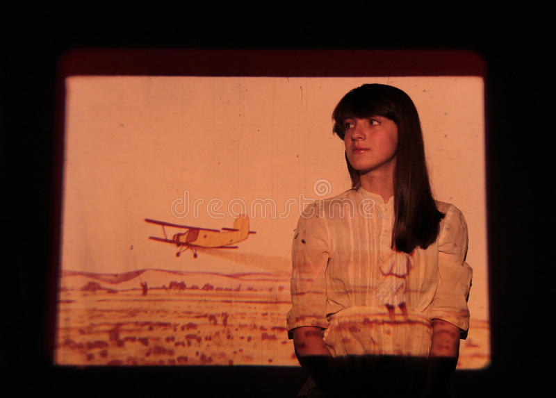 A girl and a plane - in the light of the projector stock photos