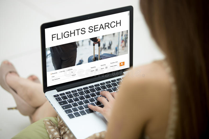 Girl planning round trip flight using laptop online. Casual young woman sitting on sofa with notebook, working on laptop computer, searching for flight using on royalty free stock photo