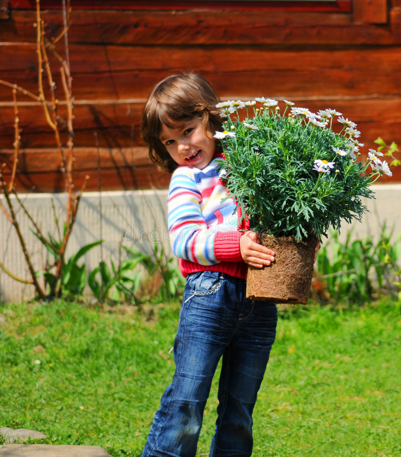 Girl planting daisies. Smiling young girl holding daisies to be planted into the ground outdoors stock image