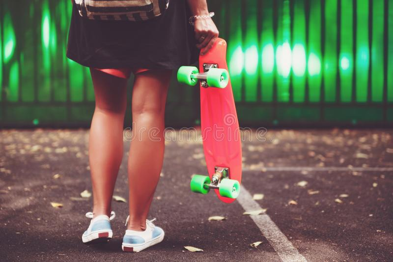 Girl with plastic orange penny shortboard behind green wall in cap royalty free stock photography